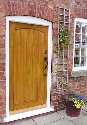 A wooden panelled barn door with arch design